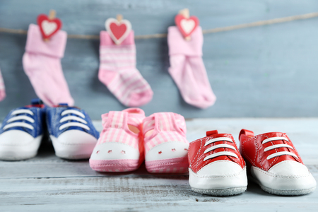 Cute toddler shoes and socks on wooden background Stock Photo