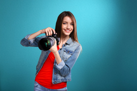 Young female photographer taking photos on blue background Standard-Bild
