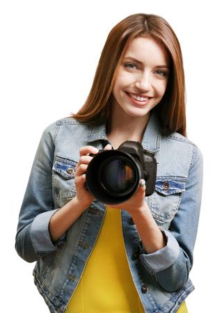 Young female photographer taking photos on grey background Standard-Bild