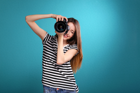 Young female photographer taking photos on blue background Stock Photo