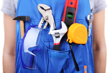 Man in coveralls with tools in his pocket, closeup Stock Photo