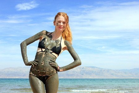 Young woman enjoying natural mineral mud sourced from Dead sea, Israel.