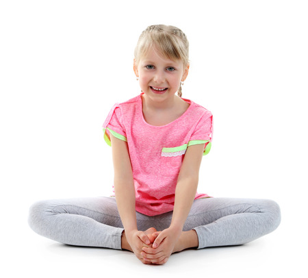 Little girl doing exercises isolated on white