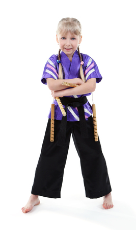 Little girl in kimono with nunchaku isolated on white Stock Photo