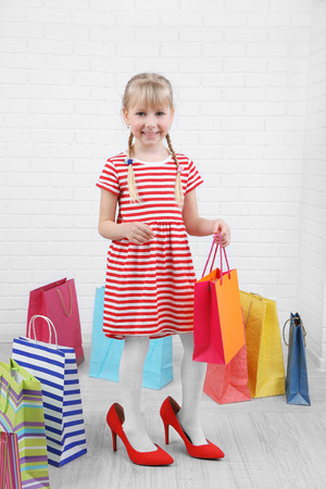 Beautiful little girl in mommy's  shoes with shopping bags in room