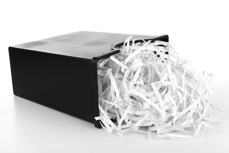 Strips of destroyed paper from shredder in trash can isolated on white Stockfoto