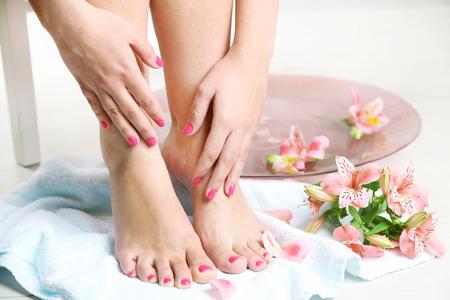 Beautiful female legs on  towel, on light  floor background Stock fotó