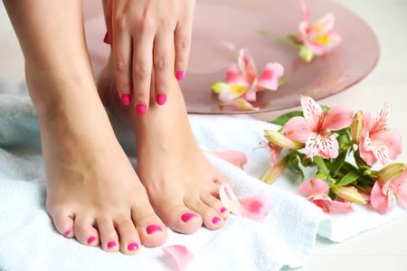 Vrouw mooie benen wassen in kom, op lichte achtergrond. Spa procedure concept