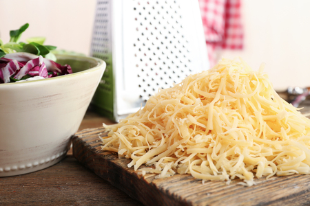 Grated cheese on wooden cutting board in kitchen Stock Photo