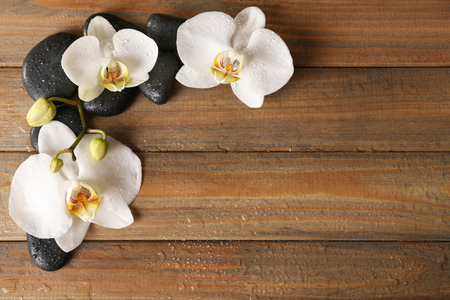 Spa stones and orchid flower on wooden background Banco de Imagens