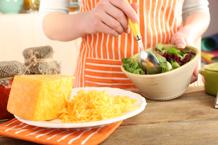 Woman cooking salad with grating cheese, close-up