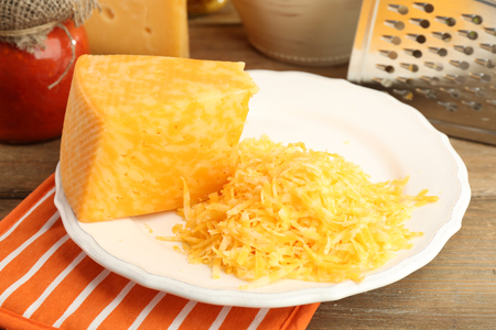 Grated cheese on wooden table, closeup