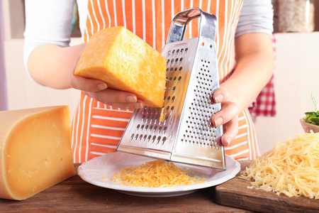 Closeup of female hands grating cheese Stock Photo