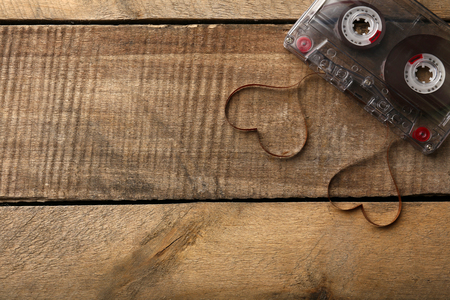 Audio cassette with magnetic tape in shape of hearts on wooden background 版權商用圖片