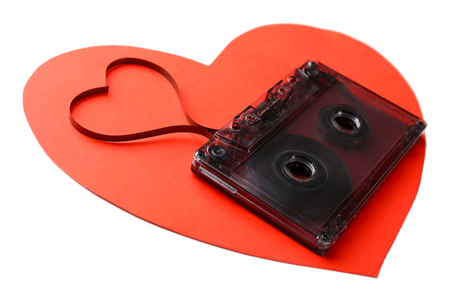 Audio cassette with magnetic tape in shape of heart close up
