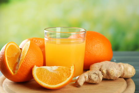 Glass of orange juice and slices on wooden table, on bright background