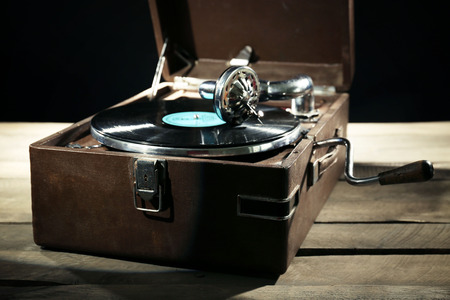 Gramophone with vinyl record on wooden table on dark background 版權商用圖片