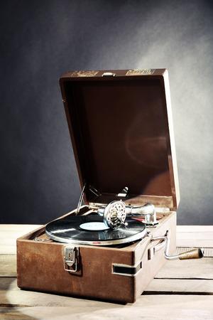 Gramophone with vinyl record on wooden table on dark background Standard-Bild
