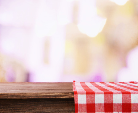 Empty wooden table with napkin on light background