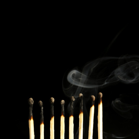 Burned matches in smoke on black background