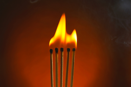 Burning matches with smoke on dark color background