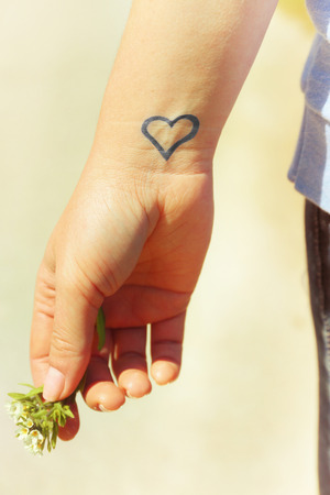 Close up of wrist of young woman with heart tattooed in it, on nature background