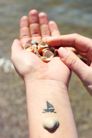 Close up of hands of young woman with ship tattooed in it, on sea background Stock Photo