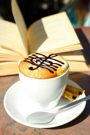 Cups of cappuccino with treble clef on foam  and book on table in cafe Stok Fotoğraf