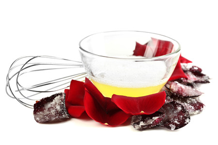 Fresh and candied sugared roses petals and egg whites, isolated on white