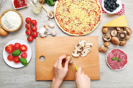 Woman making pizza on table close up
