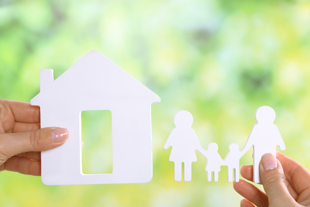 Female hands holding model of house and paper family on bright background Imagens