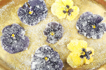 Candied sugared violet flowers on tray, close-up
