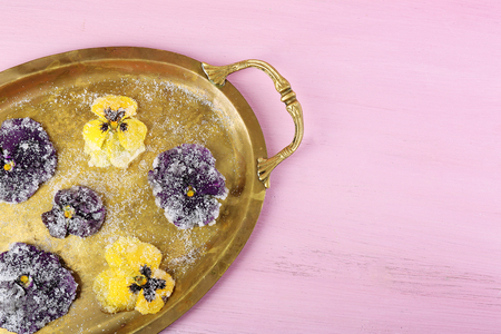 Candied sugared violet flowers on tray, on color wooden background Standard-Bild
