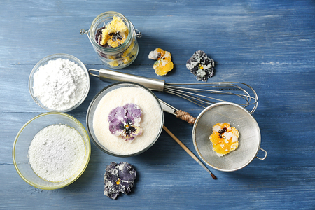 Making candied violet flowers with egg whites and sugar, on color wooden background Standard-Bild