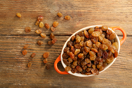 Raisins in pan on wooden table, top view