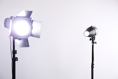 Photo studio with lighting equipment on white wall background