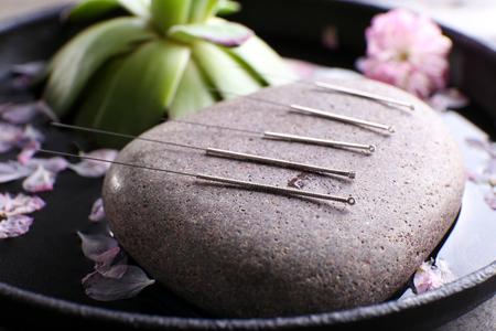 Agujas de acupuntura con piedra spa en bandeja, primer plano Foto de archivo