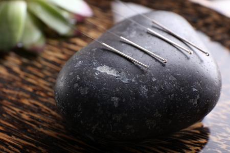 Agujas de acupuntura con piedra spa en bandeja, primer plano