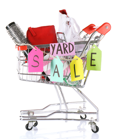 Shopping cart of unwanted stuff ready for yard sale isolated on white
