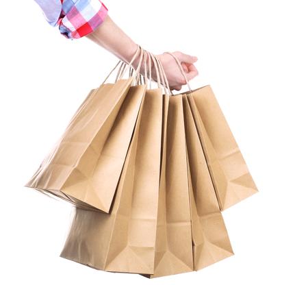 Mano femenina sosteniendo la bolsa de papel aislado en blanco Foto de archivo