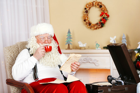 Santa Claus sitting with children letters in comfortable chair near fireplace at home Stock fotó