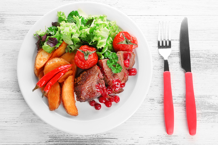 Tasty roasted meat with cranberry sauce and roasted vegetables on plate, on color wooden background Stock Photo