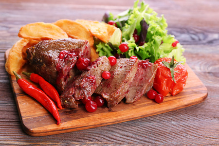Beef with cranberry sauce, roasted potato slices on cutting board, on wooden background Stock Photo