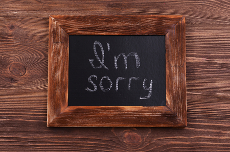 Inscription I'M SORRY on blackboard on wooden background