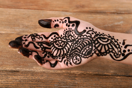 Hand painted with henna on wooden background