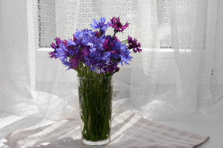 Beautiful bright bouquet in vase on fabric background
