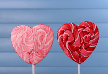 Bright lollipops in shape of heart on wooden background 스톡 콘텐츠