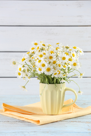Beautiful bouquet of daisies in cup on wooden background 免版税图像 - 101348629