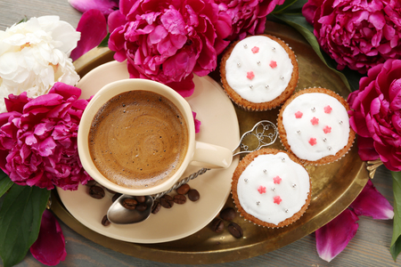 Composition with cup of coffee, muffins and peony flowers on wooden background Stock Photo