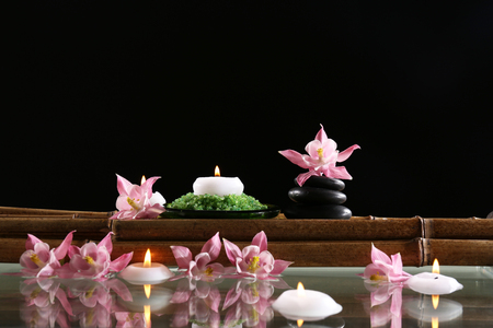 Beautiful spa composition with flowers and candles on black background Stock Photo